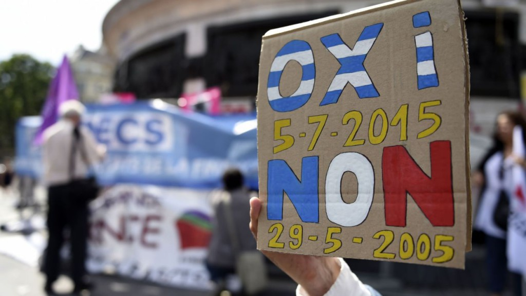 "A protester holds a sign reading ""No"" in Greek and French during a rally in support of Greece in Paris on June 28, 2015. Greece weighed drastic banking restrictions to stave off a financial collapse as anxious Greeks emptied cash machines amid fears that banks will be closed this week. AFP PHOTO / LOIC VENANCE"